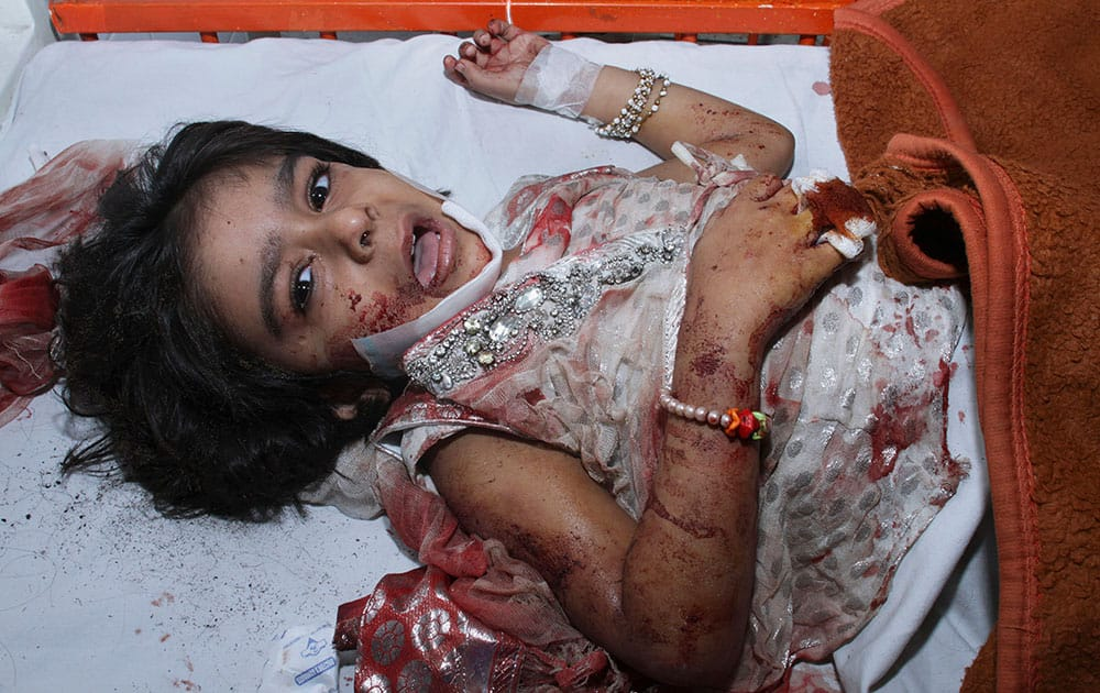 A girl injured in a bomb explosion cries while waiting for initial treatment at a local hospital in Lahore.