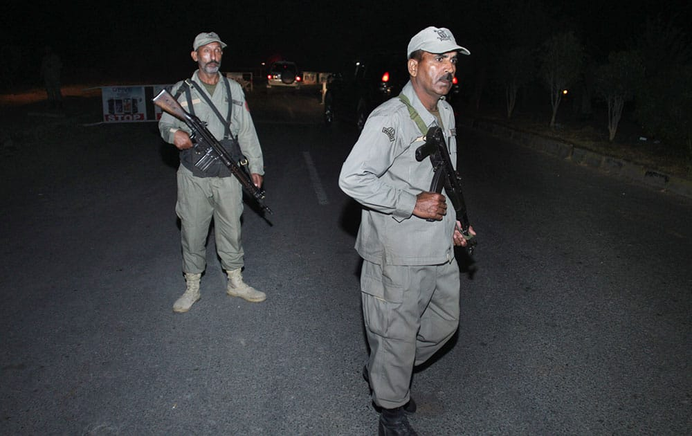 Pakistani paramilitary soldiers stand guard at a cordoned road leading to the site of a bomb explosion in Lahore.