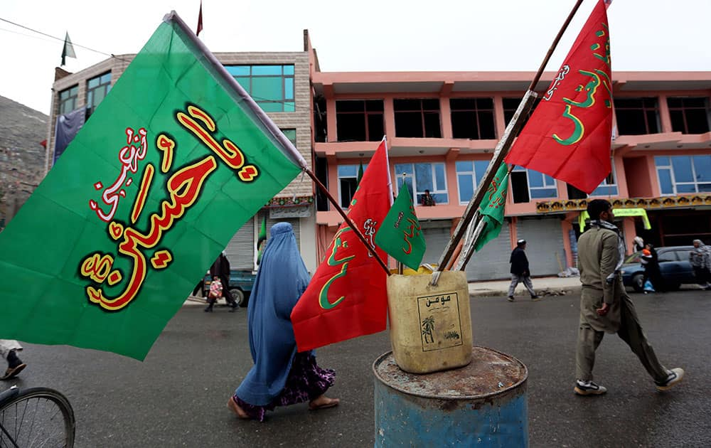 An Afghan woman walks past religious flags, ahead of the Ashoura holiday, in Kabul, Afghanistan.