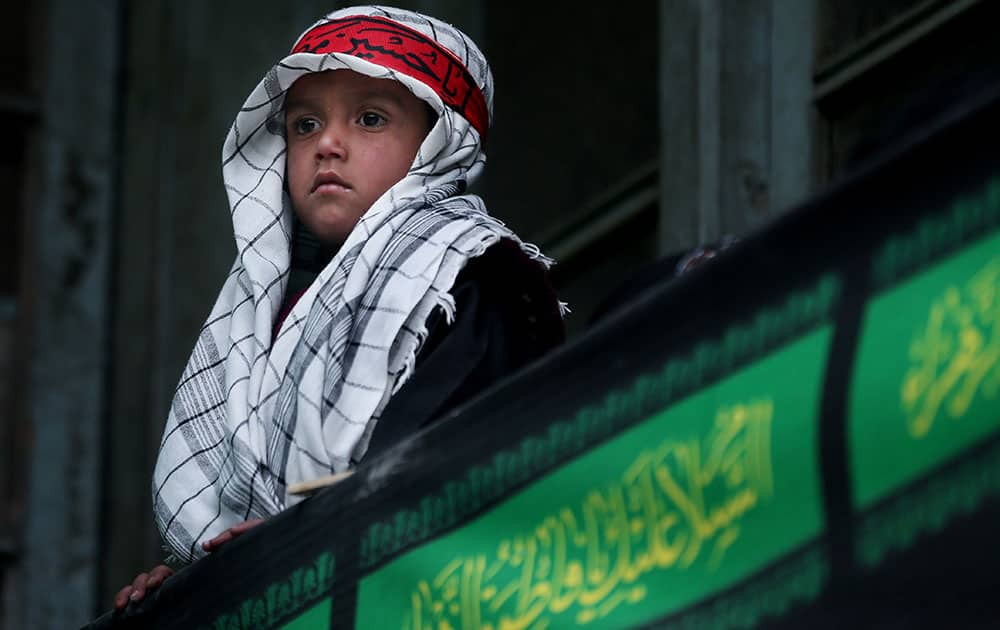 An Afghan Shiite boy watches a religious ceremony ahead of the Ashoura holiday, in Kabul, Afghanistan.