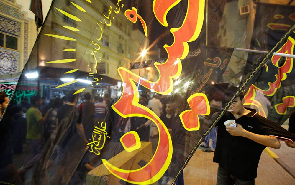 Bahraini mourners are seen through a religious flag that reads, `Oh, Hussein,` part of Shiite traditions for the Islamic month of Muharram, in Manama, Bahrain.