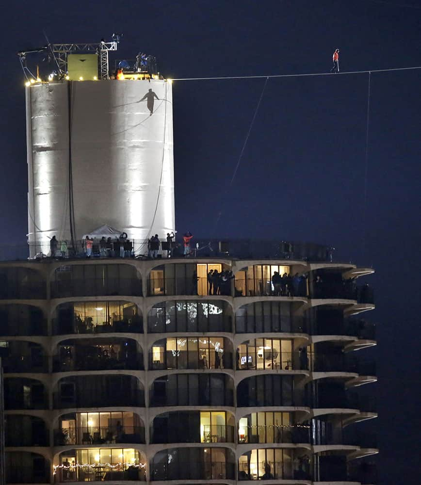 The shadow of daredevil Nik Wallenda is cast against the West Marina Tower as he begins his tightrope walk uphill at a 19-degree angle, from the Marina City west tower across the Chicago River to the top of the Leo Burnett Building in Chicago.