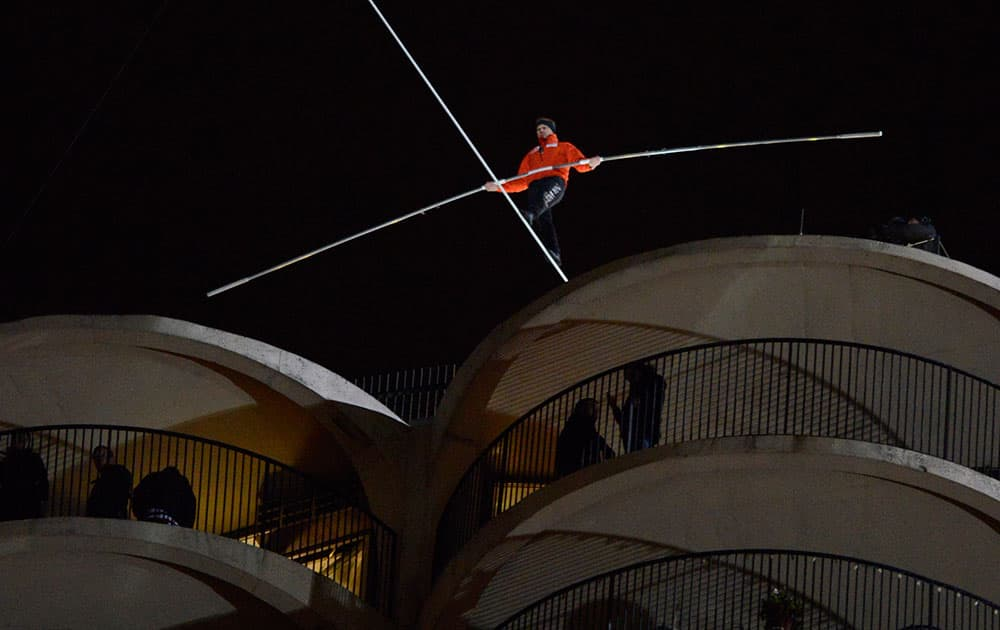Daredevil Nik Wallenda begins his tightrope walk uphill at a 19-degree angle from the Marina City west tower across the Chicago River to the top of the Leo Burnett Building in Chicago.
