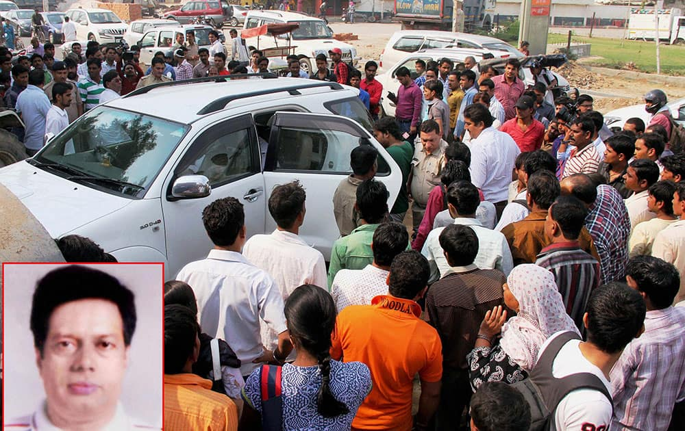 **COMBO** People gather around the vehicle in which a property dealer Virender (inset) was shot in Gurgaon.