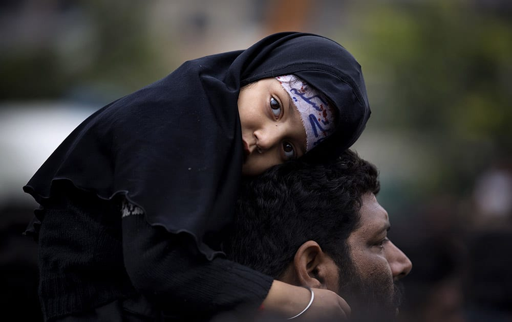 A Pakistani Shiite girl attends a mourning procession, a day ahead of Ashoura holiday during the holy month of Muharram, in Islamabad, Pakistan.