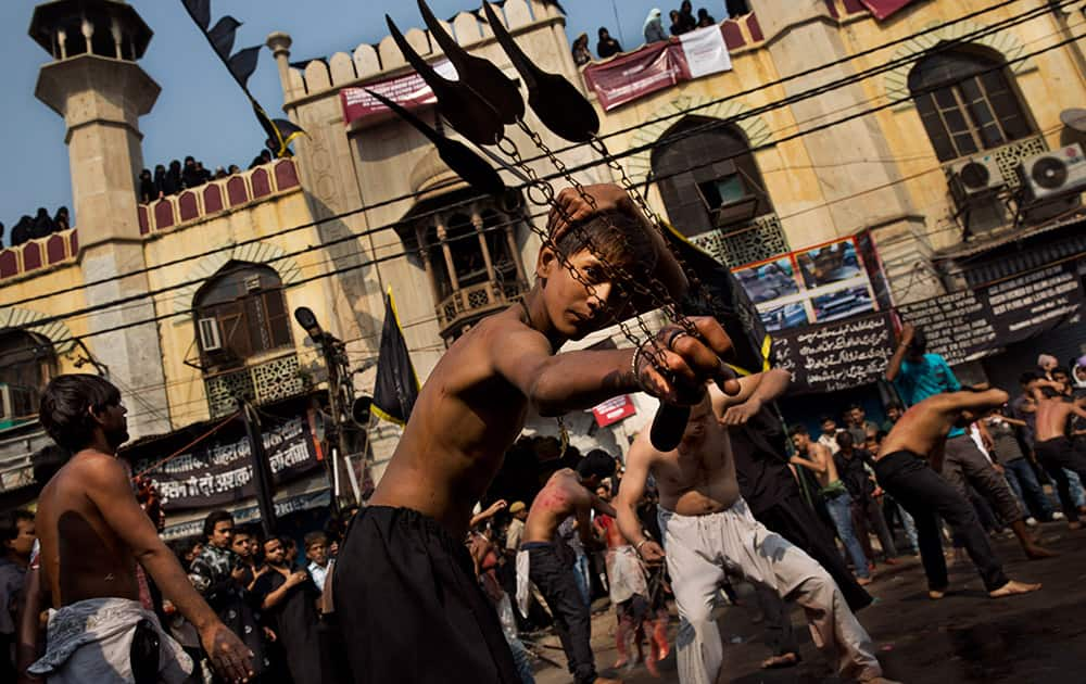 A YOUNG SHIITE MUSLIM FLAGELLATES HIMSELF DURING A PROCESSION TO MARK ASHOURA IN NEW DELHI, INDIA.
