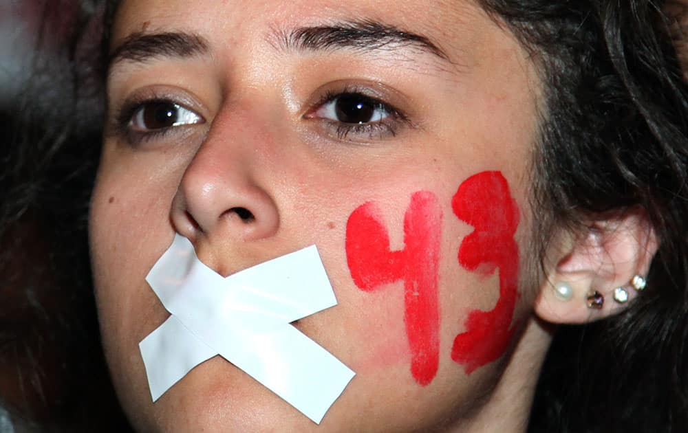 A demonstrators with her mouth taped shut and the number 43 painted on her face marches in protest for the disappearance of 43 students in the state of Guerrero, in Mexico City.