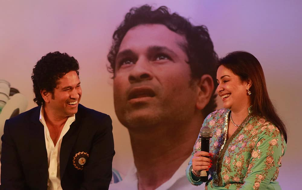 Retired cricket great Sachin Tendulkar, shares a lighter moment with his wife Anjali during the launch of his autobiography, 'Playing It My Way,' in Mumbai.