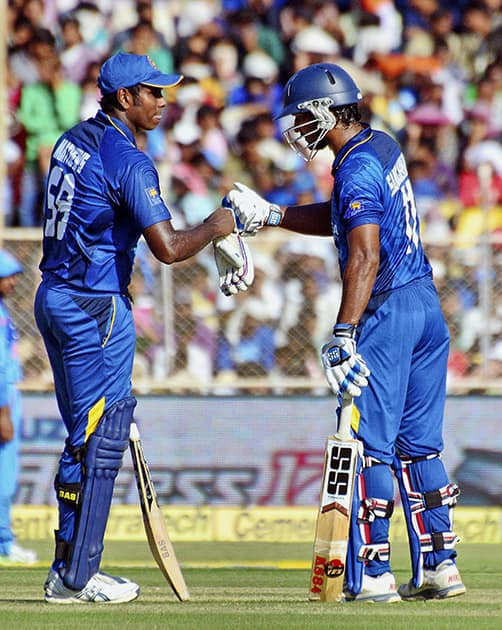 Sri Lankan batsman Angelo Mathews congratulates Kumar Sangakkara on scoring a half century during the 2nd ODI Match against India in Ahmedabad.