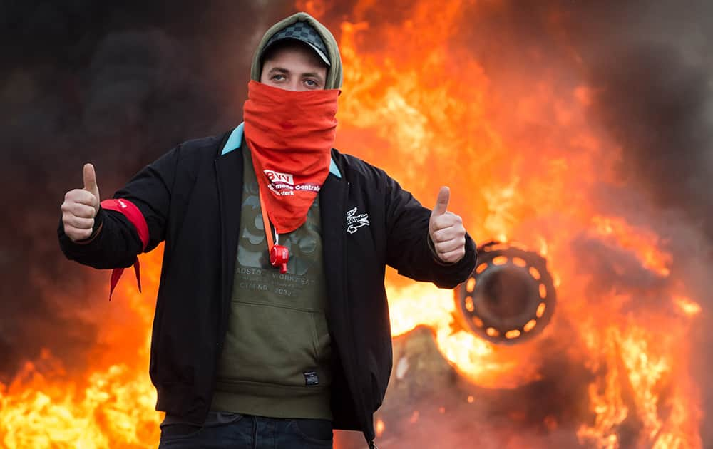 A protestor gives thumbs up as he stands in front of a burning car during a national trade union demonstration in Brussels.
