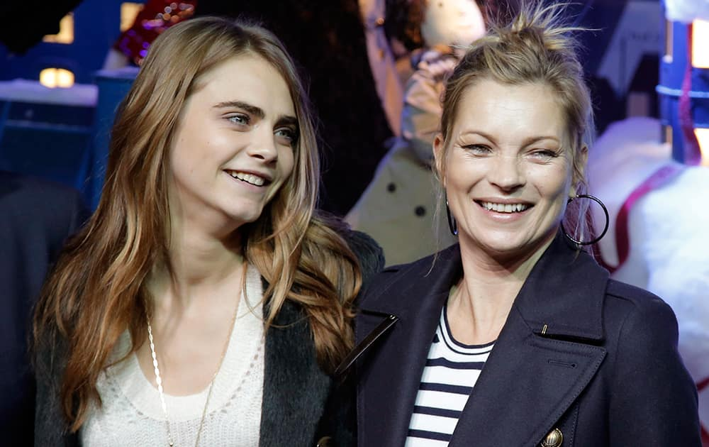 British models Cara Delevingne and Kate Moss pose during a photocall as they attend the Magical Christmas Journey event hosted by Burberry, in Paris, France.