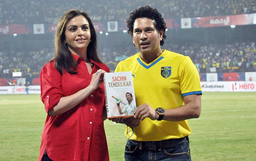 Cricket legend and Kerala Blasters FC co-owner Sachin Tendulkar with Nita Ambani showing his recently launched autobiography Playing It My Way during an ISL match in Kochi.