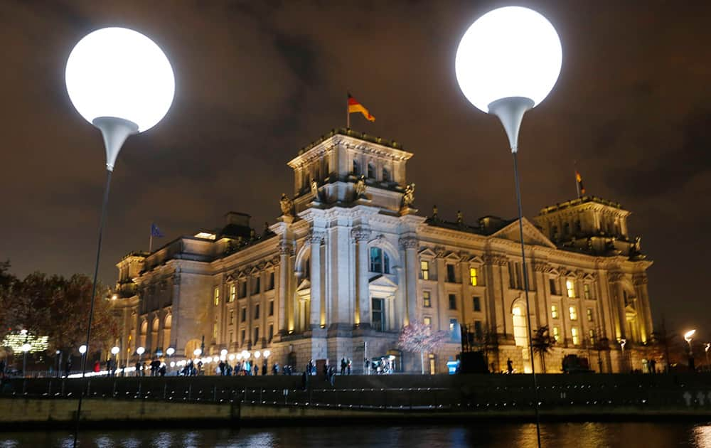 Balloons of the art project 'Lichtgrenze 2014' (lit. 'lightborder 2014') are illuminated in front of the Reichstags building in Berlin, Germany. The light installation featuring 8,000 luminous white balloons commemorates the division of Berlin where the 25th anniversary of the fall of the wall is marked with numerous events on the weekend.
