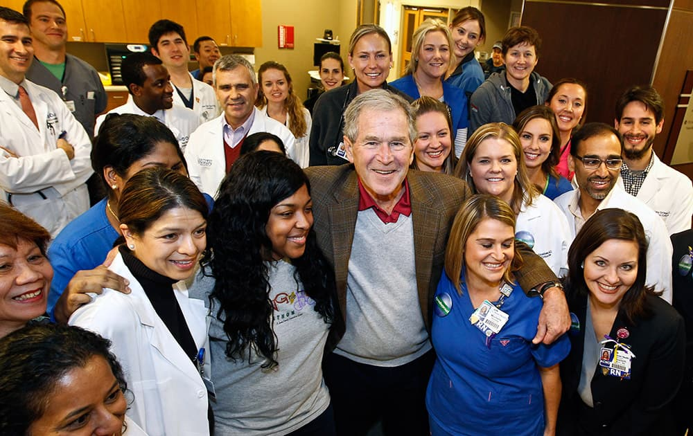This photo provided by Texas Health Resources, former President George W. Bush poses with caregivers in the Medical Intensive Care Unit at Texas Health Presbyterian Hospital.