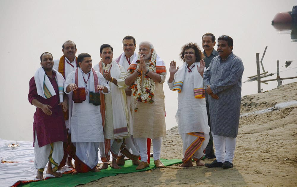 Prime Minister Narendra Modi offers prayers with priests during the launch of Namami Gange project at Assi Ghat in Varanasi.