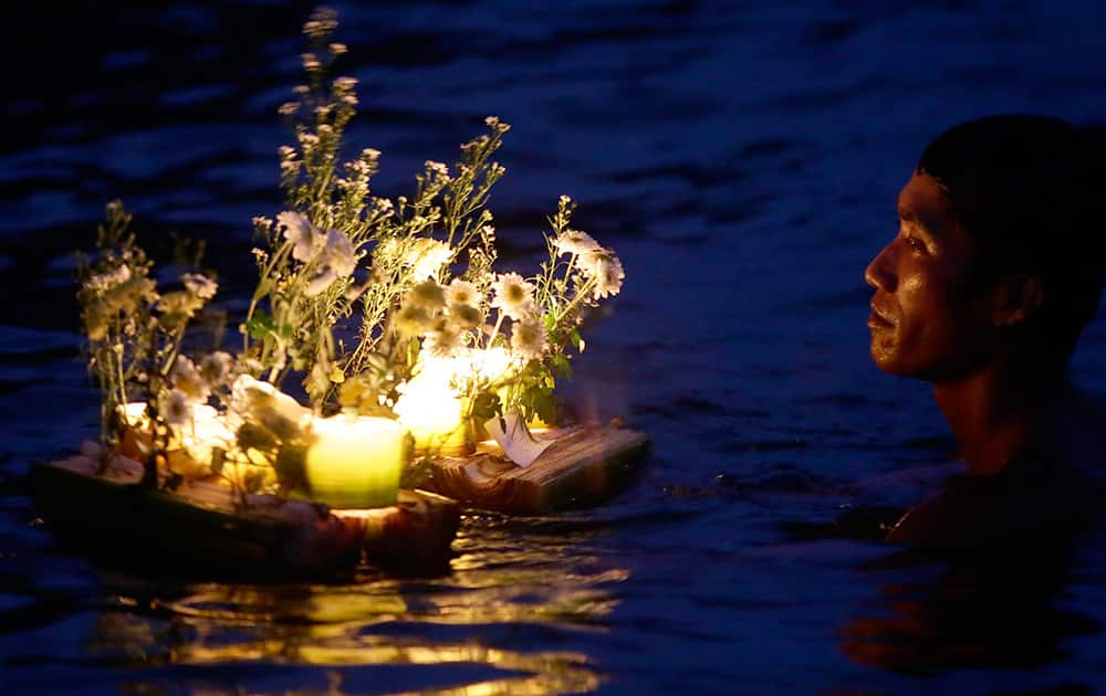 A typhoon survivor lightS candles and floats flowers at a coastal village in Tacloban city, Leyte province in central Philippines to commemorate the 1st anniversary when Typhoon Haiyan barreled inland from the Pacific in the world's deadliest disaster last year.