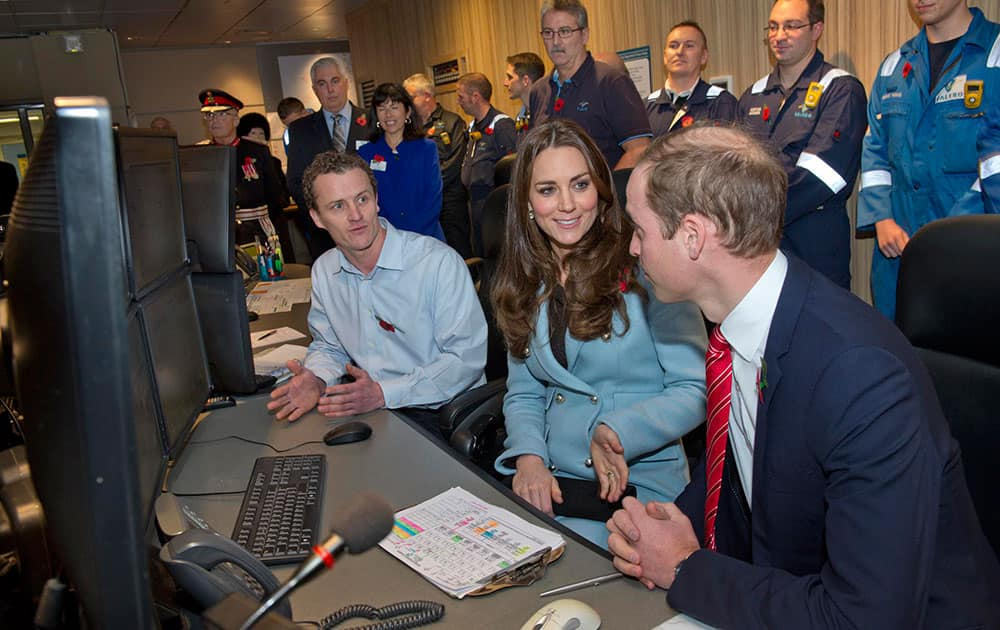 William Richards, left, shows Kate, Duchess of Cambridge and Prince William, right, the main control room at their visit to the Valero Pembroke Refinery in west Wales.