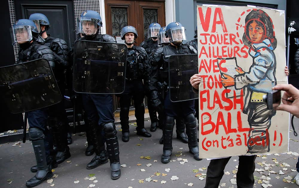 A protester holds a placard reading `Go playing away with your flashball, we keep an eye on you` during a march against police violence and in tribute to Remi Fraisse, a 21-year-old environmental activist who died during clashes between security forces and protesters of the Sivens dam project, in Paris, France.