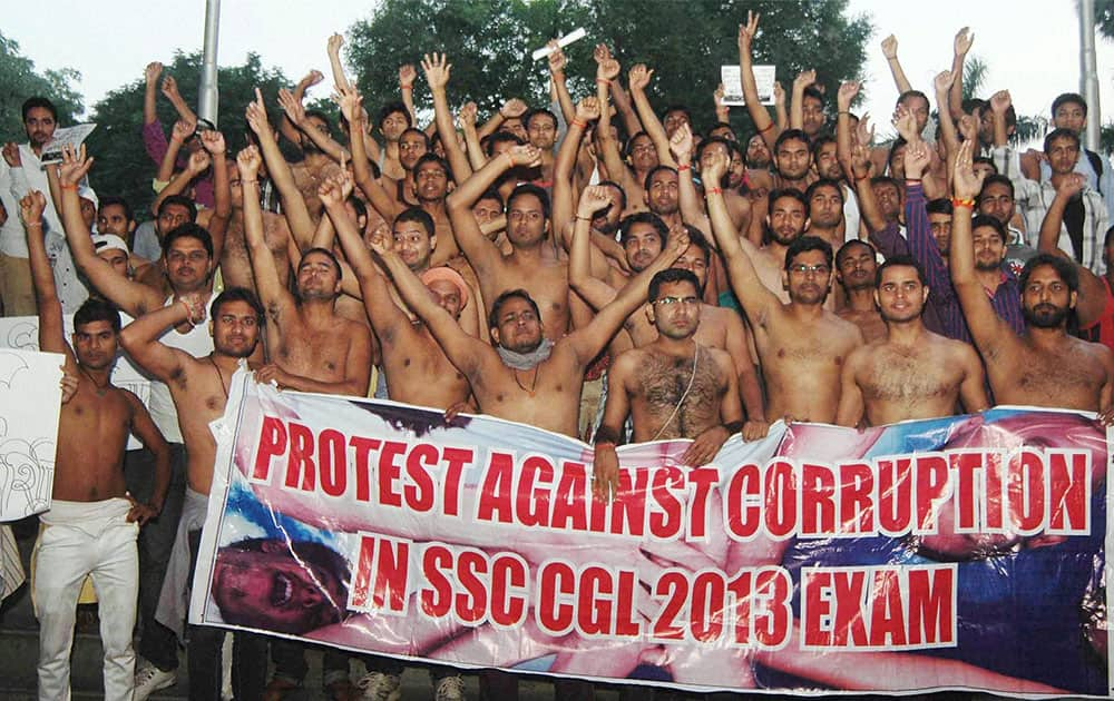 Students shout slogans and hold a poster during their protest against corruption in Combined Graduate Level Test 2013 in Allahabad.