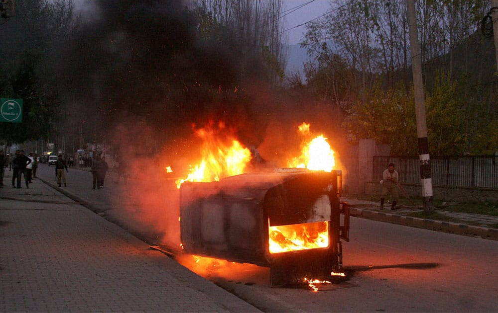 A CRPF vehicle in flames after it was set ablaze by a mob protesting against the killing of two youths by the army.