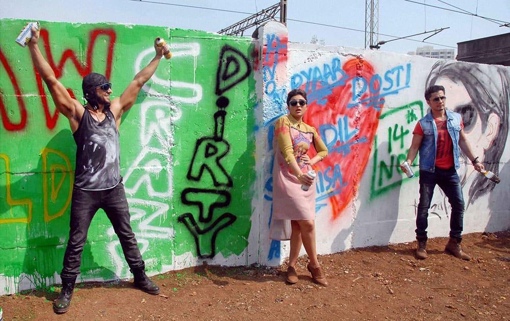 Bollywood actors Ranveer Singh, Parineeti Chopra and Ali Zafar paint graffitis on wall.