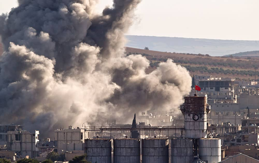 The Turkish flag flies on a grain silo backdropped by smoke in the Syrian town of Kobani, after an airstrike by the US led coalition, seen from a hilltop outside Suruc, on the Turkey-Syria border .
