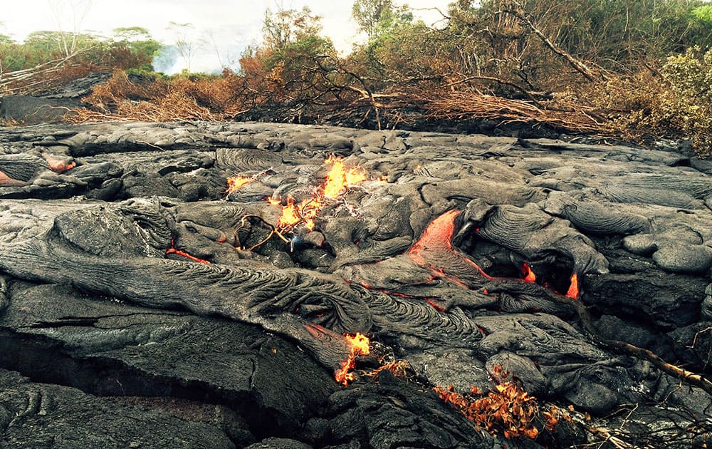 This photo from the US Geological Survey shows a breakout, or area where lava oozes to the side of a flow upslope of the stalled leading edge, about 400 meters (0.25 miles) upslope of Cemetery Road near the town of Pahoa on the Big Island of Hawaii.