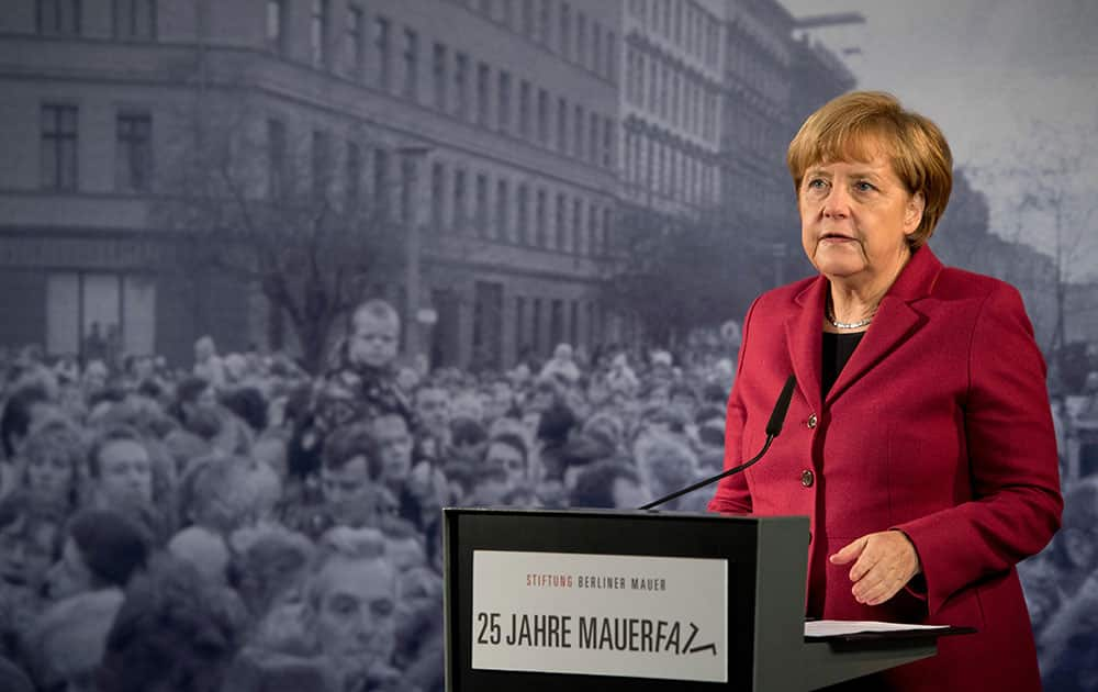 German Chancellor Angela Merkel delivers a speech in front of a historical photograph in the Berlin Wall memorial at Bernauer Strasse in Berlin, Germany.