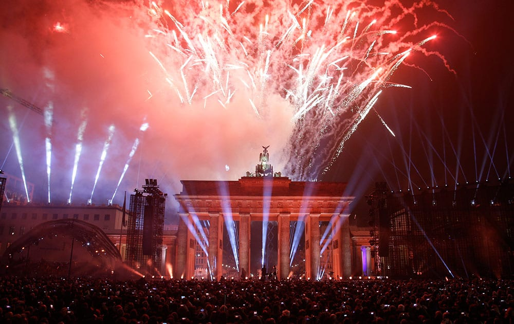 Fireworks explode behind Brandenburg Gate during the central event commemorating the fall of the wall in Berlin, Germany.