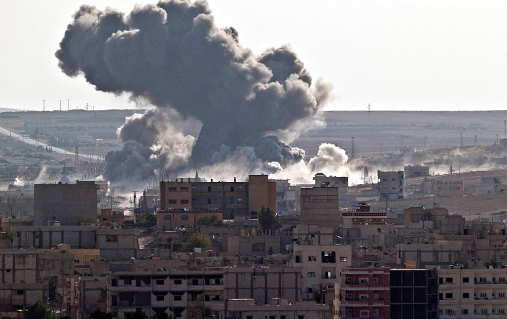 Smoke rises over the Syrian city of Kobani, following a US led coalition airstrike, seen from outside Suruc, on the Turkey-Syria border.