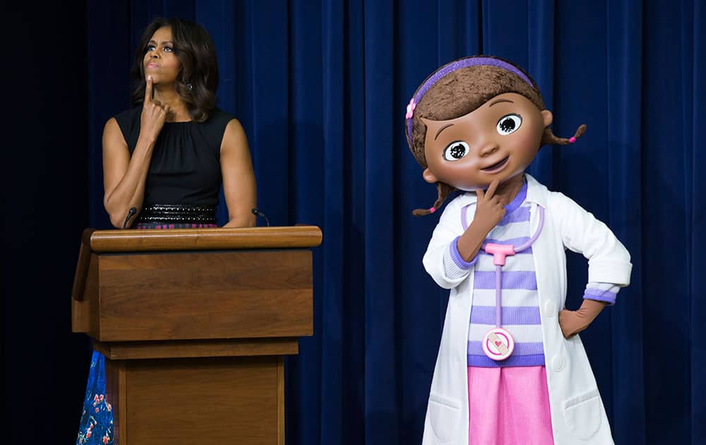 First lady Michelle Obama, left, pauses as she delivers remarks during an event with military children and families that screened a special Veteran's Day episode of Disney's `Doc McStuffins,` that explores the emotions children face when a parent is deployed, at the White House complex, in Washington.