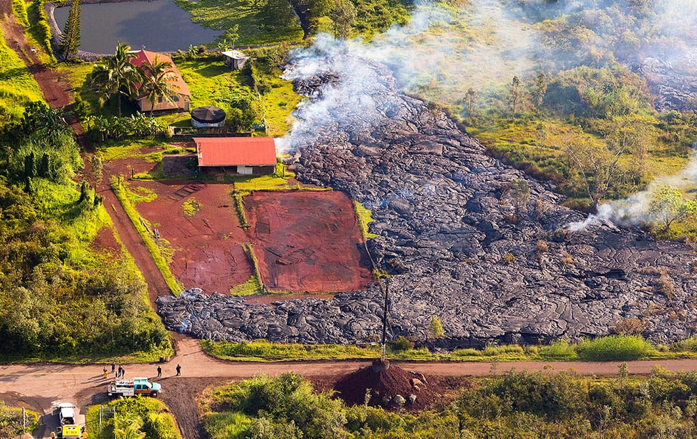 This photo released by The County of Hawaii via Ena Media Hawai'i/Blue Hawaiian Helicopters shows lava flow from the Kilauea Volcano near a residential structure in Pahoa, Hawaii.