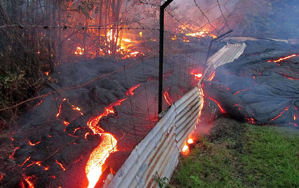 This photo taken and released by the US Geological Survey, shows lava from an upstream lobe, that was active in the forest below the Pahoa cemetery, overcoming a fence marking a private property line near the town of Pahoa, Hawaii.