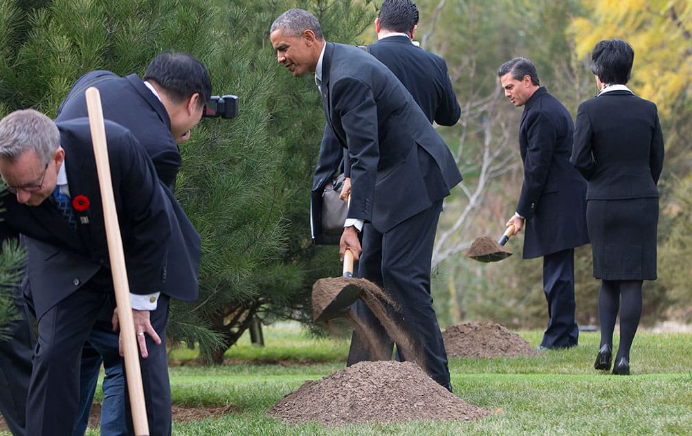 US President Barack Obama, center, Mexican President Enrique Pena Nieto, right, and Canadian Minister of Trade, Ed Fast, left, join other world leaders during a tree planting ceremony at Friendship Lawn, Yanqi Lake for the Asia-Pacific Economic Cooperation (APEC) Summit, in Beijing.