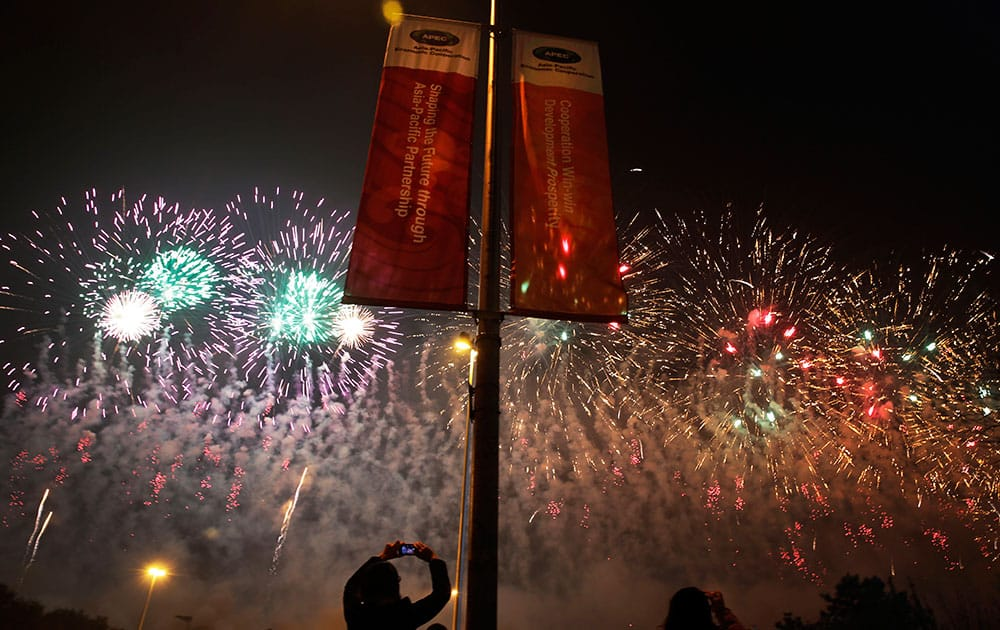 A woman uses a mobile phone to take picture of fireworks near the China National Convention Center following the welcome banquet for the Asia Pacific Economic Cooperation (APEC) summit in Beijing.