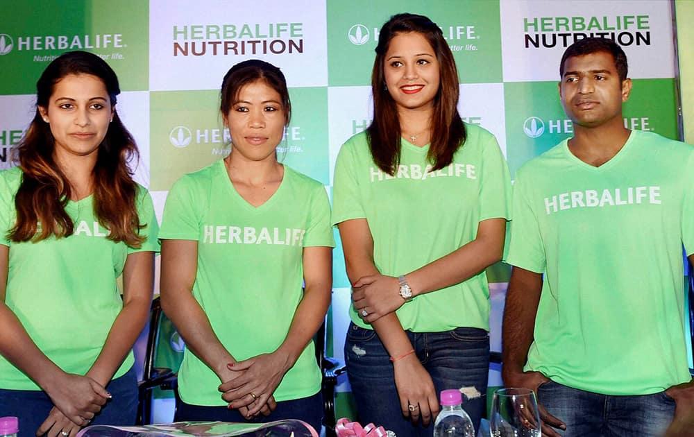 Indias Boxing Champion Mary Kom (C), Squash Champion Dipika Pallikal (2R), Pistol Shooter Heena Sidhu(L) and Paralympic high jumper H N Girish (R) at an event in Kolkata.