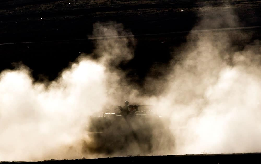 A Turkish military mobile artillery vehicle is engulfed by dust as it maneuvers on a hill overlooking the Syrian city of Kobani, outside Suruc, on the Turkey-Syria border.