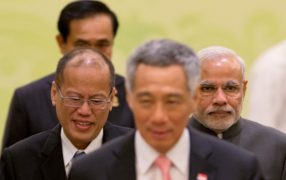 Prime Minister Narendra Modi, Philippine President Benigno Aquino III, and Singaporean Prime Minister Lee Hsien Loong, walk back to their seats after posing for a group photo during the 12th ASEAN-India summit at the Myanmar International Convention Center in Naypyitaw, Myanmar.