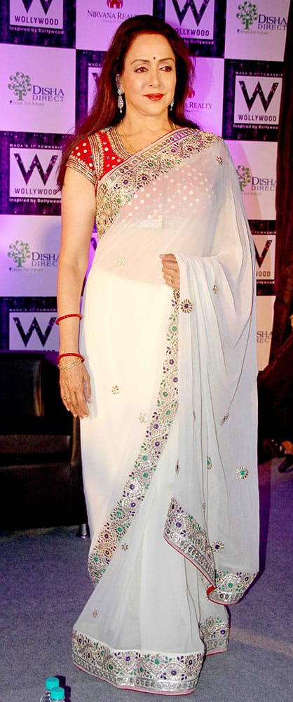 Hema Malini looked elegant in a white sari which she offset with a red embellished blouse at a brand event.- DNA