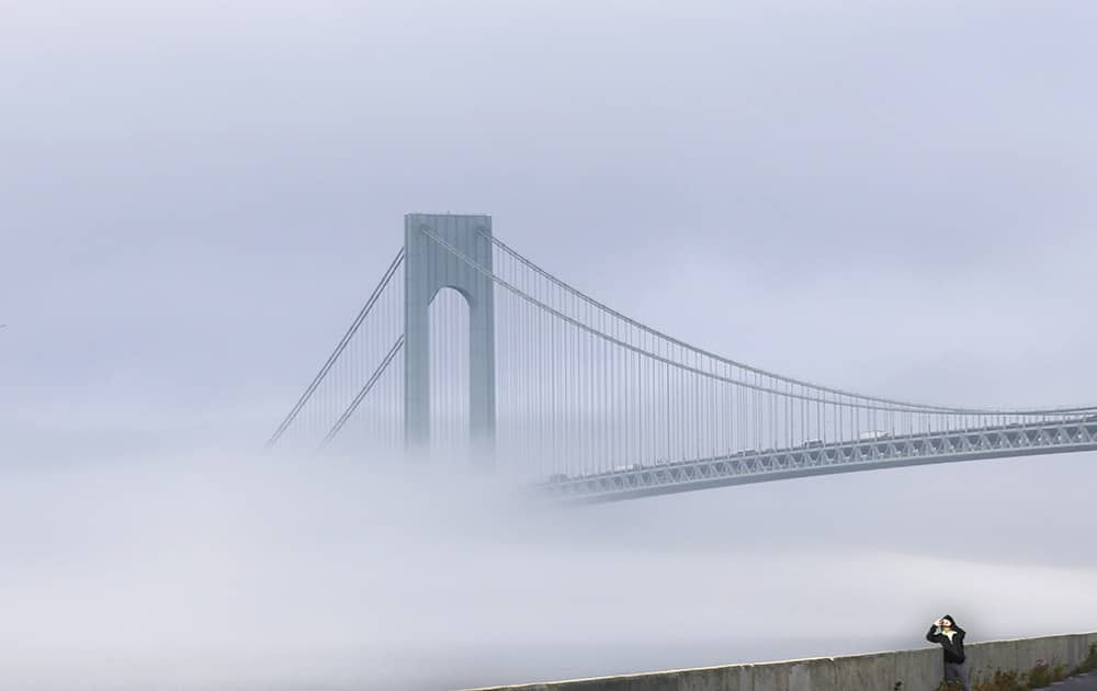 A man stops to take a picture of the foggy landscape in front of the Verrazano-Narrows Bridge in New York.