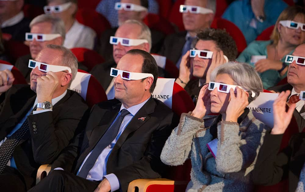 French National Centre for Space Studies (CNES) president Jean-Yves Le Gall, left, French President Francois Hollande, center, and former French minister and astronaut Claudie Haignere, right, wear 3D glasses as they visit the Cite des Sciences at La Villette during a broadcast of the Rosetta mission as it orbits around comet 67/P Churyumov-Gersimenko in Paris.