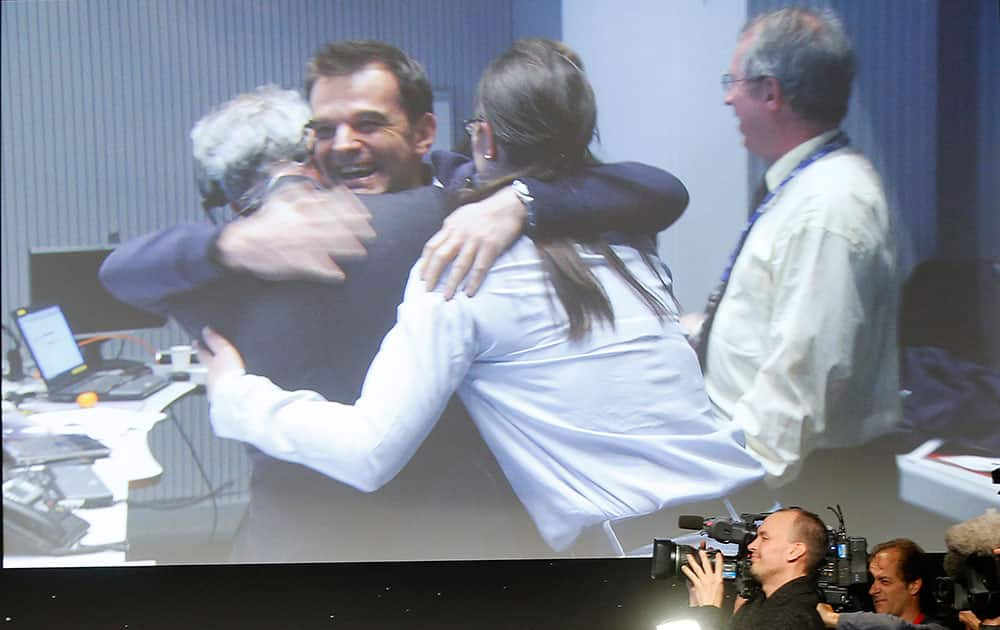 Celebrating scientists in the main control room appear on a video screen at the European Space Agency after the first unmanned spacecraft Philae landed on a comet called 67P/Churyumov-Gerasimenko, in Darmstadt, Germany