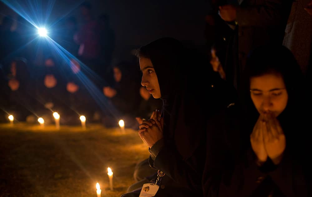 Kashmiri schoolgirls pray during a candle light vigil for flood victims in Srinagar.