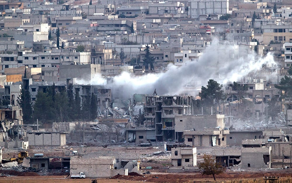 Smoke rises in the Syrian city of Kobani, seen from a hilltop outside Suruc, on the Turkey-Syria border.