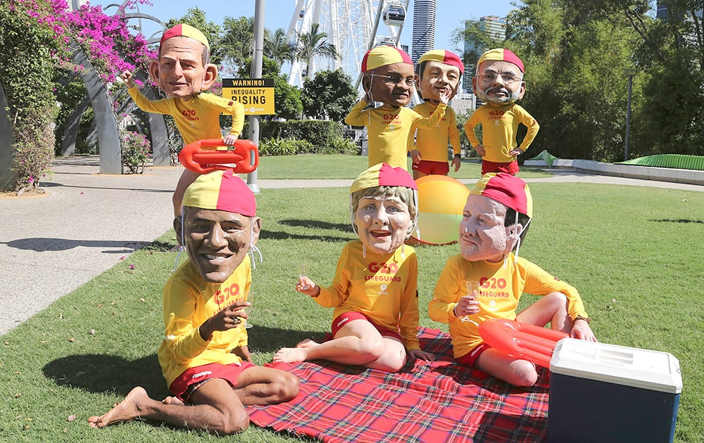 Demonstrators wearing large caricature heads of world leaders, Australian Prime Minister Tony Abbott, South African President Jacob Zuma, Chinese President Xi Jinping, Indian Prime Minister Narendra Modi, US President Barack Obama, German Chancellor Angela Merkel and British Prime Minister David Cameron pose for a photo dressed as life guards ahead of the G-20 summit in Brisbane, Australia.