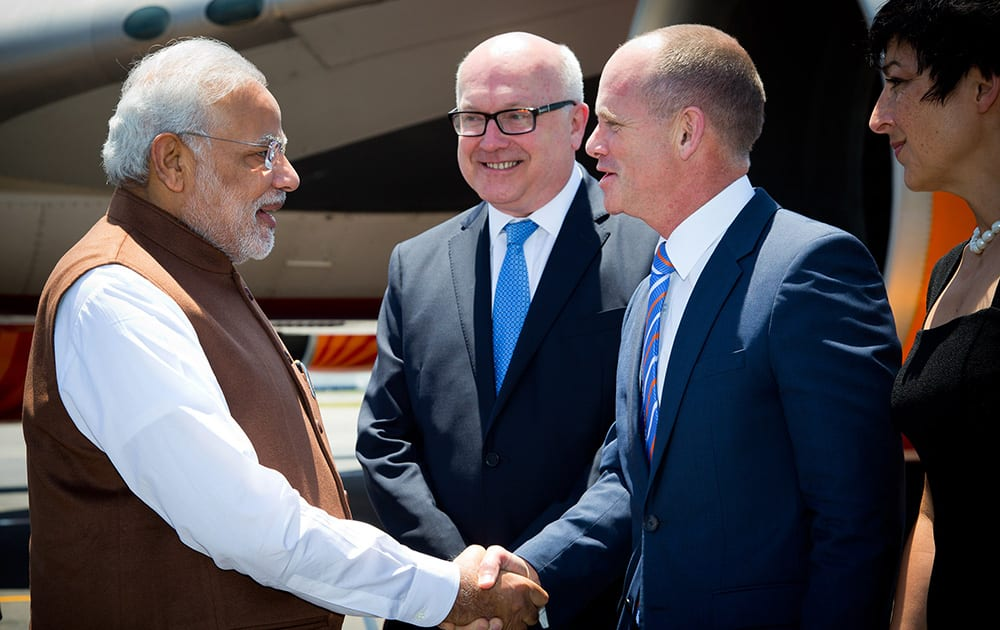 PM Narendra Modi, is welcomed by Queensland's Premier Campbell Newman as Australia's Attorney-General George Brandis looks on at Brisbane Airport ahead of the G-20 summit in Brisbane, Australia.
