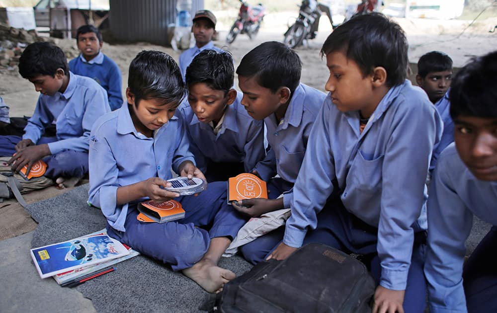 Students of a free school run under a mass transit bridge for impoverished children look at solar lanterns donated by a US donor in New Delhi.