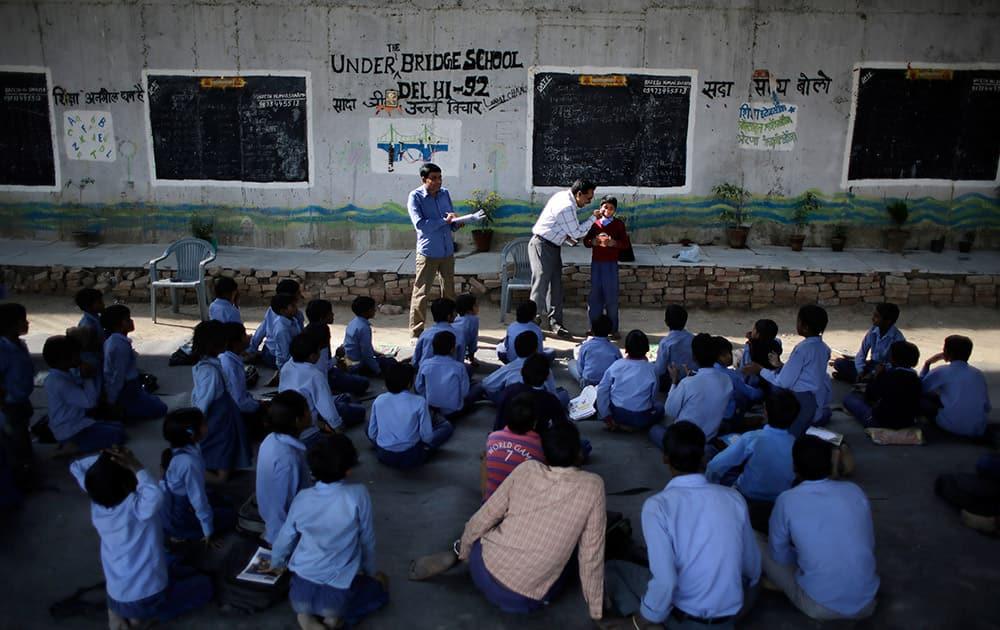 Rajesh Kumar, teacher and founder of a free school for slum children run under a metro bridge, distributes solar lanterns donated by a US donor in New Delhi.