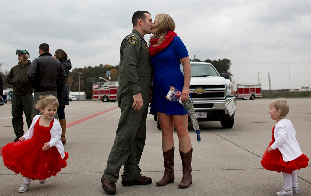 Lt. Doug DeVuono, kisses his wife, Kim, as their two daughters, Leah, 3, and Ava, 18-months, run around the them on his arrival to Naval Air Station Oceana in Virginia Beach, Va.