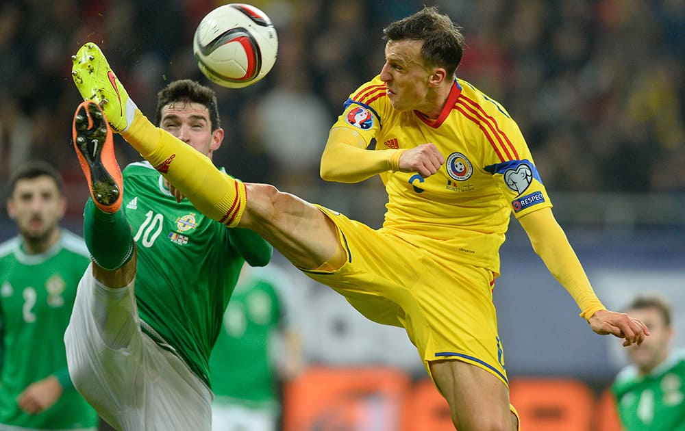 Romania's Vlad Chiriches and Northern Ireland's Kyle Lafferty, challenge for the ball during a Group F, Euro 2016 qualifying soccer match between Romania and Northern Ireland, at the National Arena stadium in Bucharest, Romania.